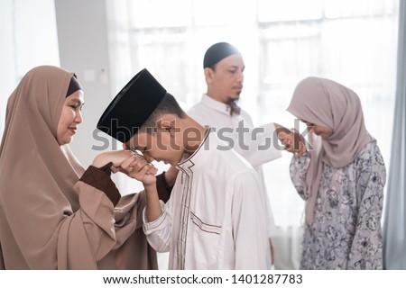 asian muslim parent shake hand in idul fitri eid mubarak celebration. family islam tradition #1401287783