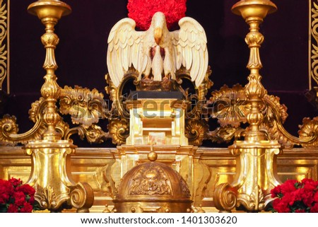 SEVILLE, SPAIN -April 9, 2019:  Beautiful ancient wooden sculpture depicting the image of Pelican and babies on the altar inside Church of El Divino Salvador #1401303620