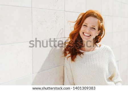 Smiling beautiful young red-haired woman in knitted sweater standing outdoor in sunny day, leaning on white tiled wall and looking at camera. Front portrait with copy space #1401309383