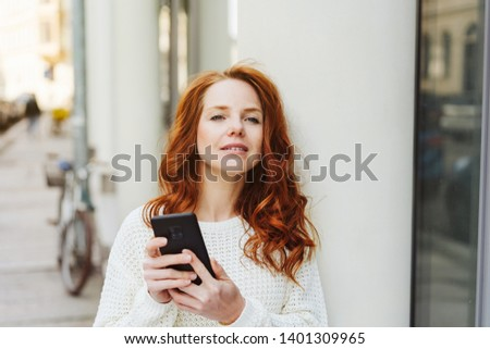 Young woman waiting in town for a meeting holding her mobile phone and peering expectantly down the street #1401309965