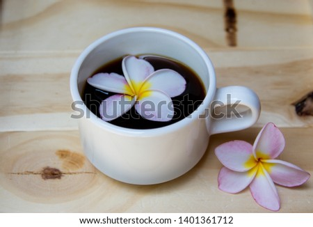 Pink Frangipani Flower In a cup of coffee with a wooden background #1401361712