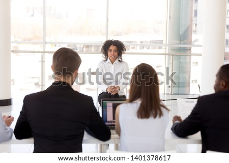 Confident African American female applicant sitting in front of diverse multiethnic HR managers, recruiters at job interview, answer at interviewer questions, candidate for vacancy, employment concept #1401378617