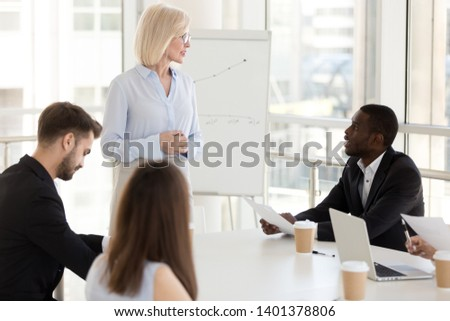 African American male employee ask question to middle-aged female coach, serious mature boss holding briefing, answer worker question about documents, business strategy, marketing plan in boardroom #1401378806