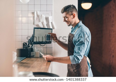 Checking the bill. Positive young waiter in a brown apron smiling and looking at the bill while standing at the bar counter #1401388337