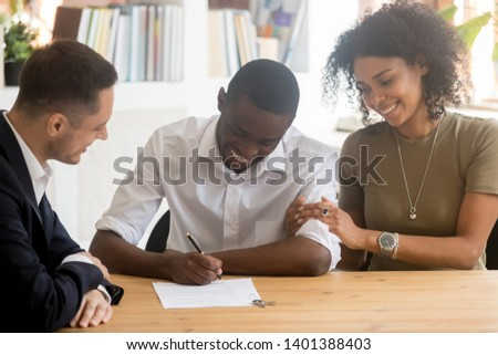 Happy black millennial couple sign contract closing deal with real estate agent buying home together, excited african American husband put signature on agreement rent take loan with wife at broker #1401388403