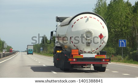 Semi truck with propane tank moving on asphalt road on a summer day - ADR dangerous cargo, side rear view Royalty-Free Stock Photo #1401388841