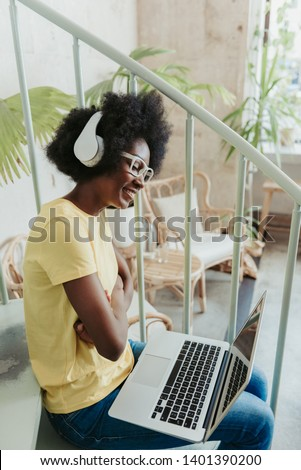 Waist up of beautiful American girl wearing yellow T-shirt and listening to music indoors. She is sitting with crossed hands and looking at screen of digital gadget #1401390200