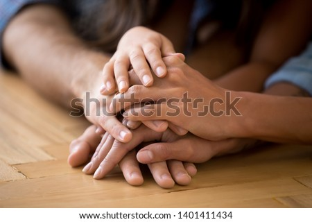 Close up of loving family stack hands on warm floor together show support and unity, caring parents join arms with child express devotion loyalty understanding. Bonding, good relationships concept #1401411434