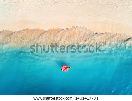 Aerial view of a young woman swimming with the donut swim ring in the clear blue sea with waves at sunset in summer. Tropical aerial landscape with girl, azure water, sandy beach. Top view. Travel #1401417791