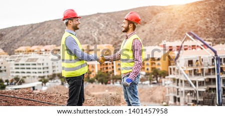 Builders on residential construction site making a deal - Happy workers are satisfied of their plan - Dealing, real estate, engineer, industrial and building houses concept #1401457958