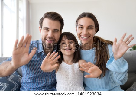 Happy parents sit on couch at home with cute little daughter wave talk on webcam, smiling young family with preschooler girl kid have conversation or shoot record vlog for social media together #1401523034