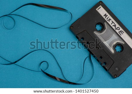 Cassette with mixtape written isolated against blue background