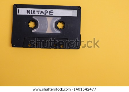 Cassette with mixtape written isolated against yellow background