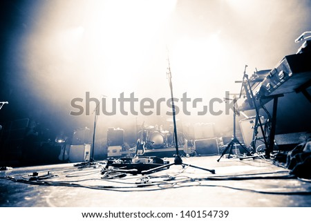 Empty illuminated stage with drumkit, guitar and microphones Royalty-Free Stock Photo #140154739