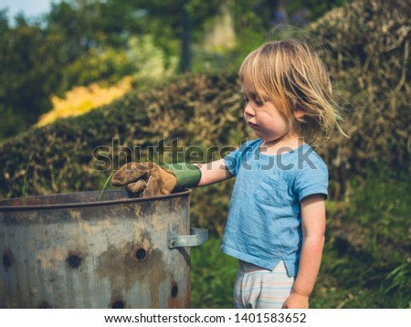 A little toddler is gardening and putting weeds in an incinerator #1401583652