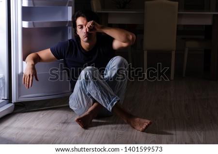 Man breaking diet at night near fridge #1401599573