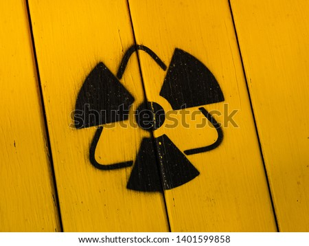 Radioactivity sign, close-up. Sign of radiation on a yellow wooden board. Radioactive sign - symbol of radiation. Yellow and black radioactive hazard, ionizing radiation, nuclear danger warning symbol #1401599858