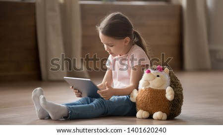 Cute little girl sit on warm home floor with hedgehog toy hold tablet playing children game, funny preschooler child have fun relax with plush teddy friend using pad watching cartoon or video