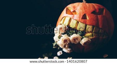Evil pumpkin devouring flowers. Halloween decor. #1401620807