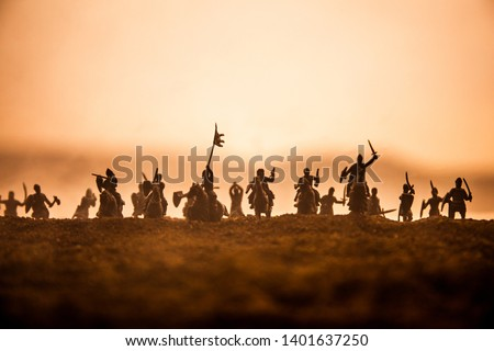 Medieval battle scene with cavalry and infantry. Silhouettes of figures as separate objects, fight between warriors on sunset foggy background. Selective focus Royalty-Free Stock Photo #1401637250