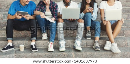 Teen pastime. Group of teenagers spending time outdoors, sitting with gadgets on stairs, panorama Royalty-Free Stock Photo #1401637973