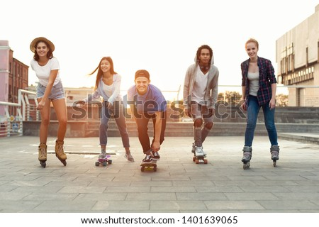 Cool teen friends. Happy teenagers having fun, riding on skateboards and rollers on summer evening #1401639065