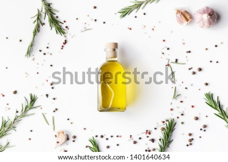 Olive oil in bottle, scattered spices and herbs on white background, top view. Food background concept #1401640634