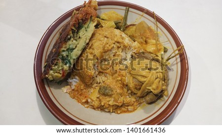 """Nasi Padang or """"Padang Rice"""" is a famous traditional food  from indonesia with curry gravy, young jackfruit and cassava leaves, fried egg, chicken, sambal hijau or spicy sauce #1401661436"""