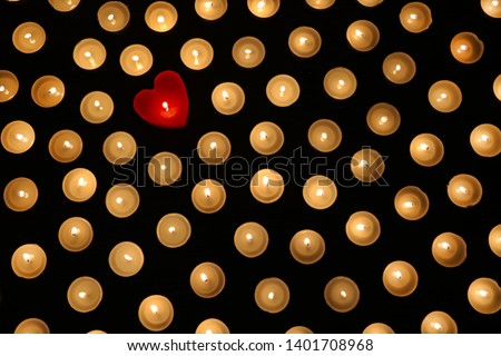 Many burning tea light candles, one candle in form of heart, concept of separating from the crowd and problem of individuality #1401708968