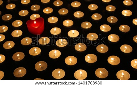 Many burning tea light candles, one candle in form of heart, concept of separating from the crowd and problem of individuality #1401708980