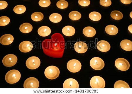 Many burning tea light candles, one candle in form of heart, concept of separating from the crowd and problem of individuality #1401708983