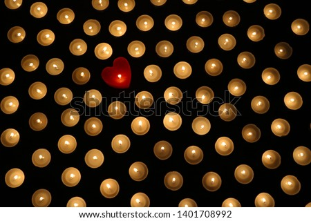 Many burning tea light candles, one candle in form of heart, concept of separating from the crowd and problem of individuality #1401708992