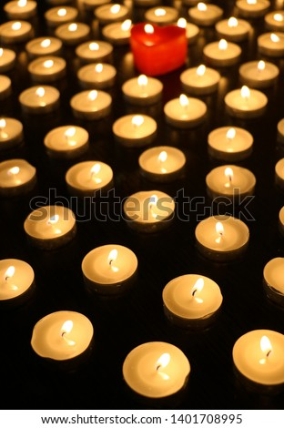 Many burning tea light candles, one candle in form of heart #1401708995
