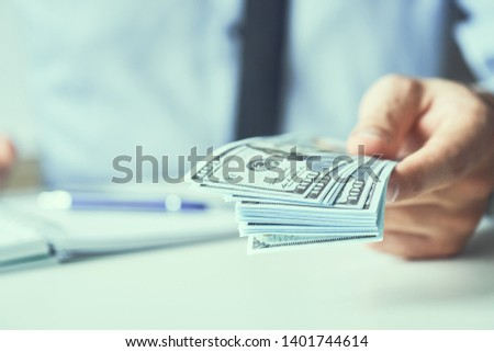 Man giving money us dollar banknotes and holding cash in hands. Money credit concept. Toned picture.