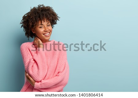 Studio shot of glad charming young female with Afro haircut, touches neck, wears oversized jumper, isolated over blue background with blank space for your promotional content. Pleasant emotions #1401806414