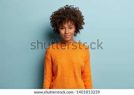 Portrait of satisfied dark skinned female model with Afro haircut, gentle smile, dressed in casual orange jumper, looks straightly at camera, pose over blue studio wall for making photo. Ethnicity #1401813239