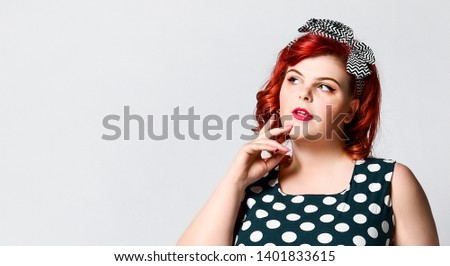 Portrait of a pretty pretty girl in pin-up size plus looking thoughtfully at the side of an empty advertising space #1401833615