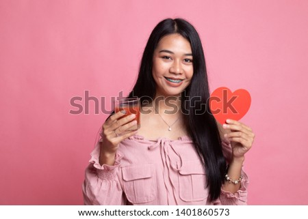 Young Asian woman with tomato juice and red heart on pink background #1401860573