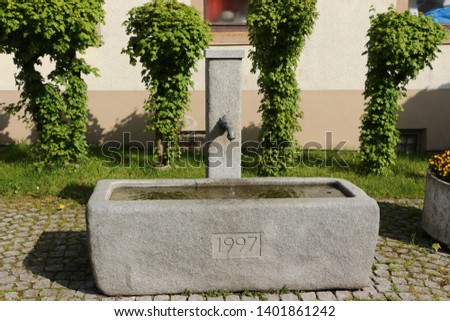 Old fountain in the center of a small town in the Wiesental in the Black Forest in Germany #1401861242