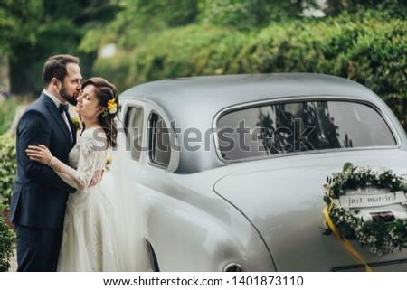 Happy luxury wedding couple kissing and embracing near retro car.  #1401873110