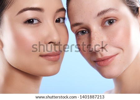 Portrait of young pretty Asian and Caucasian ladies with different types of skin standing opposite each other and looking at camera in studio. Beauty, facial treatment and spa concept