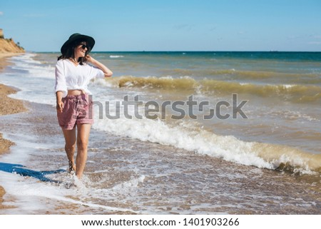 Summer vacation. Happy young boho woman walking in sea waves in sunny warm day at tropical island and blue sky. Space for text. Stylish hipster girl in hat  relaxing on beach and smiling. #1401903266