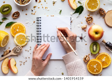 Female hand write in notebook on healthy food background, women diet nutrition recipe menu, fresh summer fruit granola seeds on white table organic super food, health care detox, top view, copy space Royalty-Free Stock Photo #1401914159