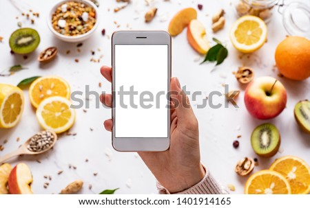 Female hands holding smartphone on healthy food background, woman using phone search mobile apps with diet nutrition plan cooking, vegan fruit granola seeds on white table, top view, mock up screen #1401914165