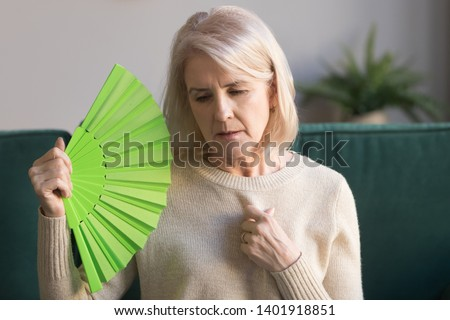 Overheated elderly woman sitting on couch waving green fan to cool herself, sixty years female feels unwell hot, age hormonal changes, apartments without air conditioner, summertime discomfort concept #1401918851