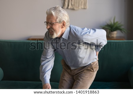 Aged grey haired sixty years man in glasses writhes in pain suffers from low back strain, touch rubbing or massaging loin reduces backache. Degenerative disk disease, pinched nerve rheumatism concept #1401918863