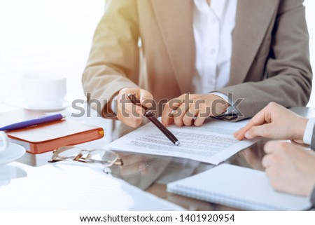 Group of business people or lawyers discussing contract papers sitting at the table, close-up #1401920954