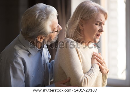 Close up focus on elderly wife hold hand on breast touch chest having heart attack feels unwell, worried husband supporting her, myocardial infarction symptoms, immediately emergency call need concept Royalty-Free Stock Photo #1401929189