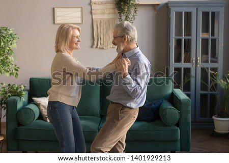 Aged funny laughing wife and husband holds hands standing in living room listening rhythmic music favourite song dancing enjoy weekend, spouses celebrate anniversary romantic date feels happy concept #1401929213