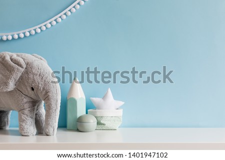 Cozy scandinavian newborn baby room with gray plush elephant ,white stars lamp and children accessories. Stylish interior with blue walls and haniging white garland. Template. Copy space.  #1401947102